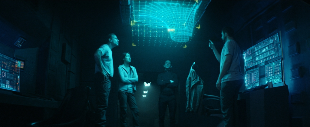 Captain McKay (David M. Edelstien), Moira, Cole and Andrew Jensen (Ben Kliewer) study a holographic display that offers clues as to their predicament.