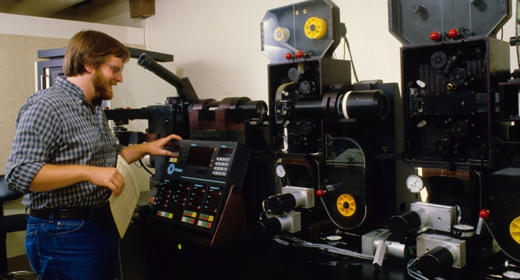 """Ken Smith at the controls of ILM's """"Workhorse"""" optical printer. Photograph courtesy of ILM."""